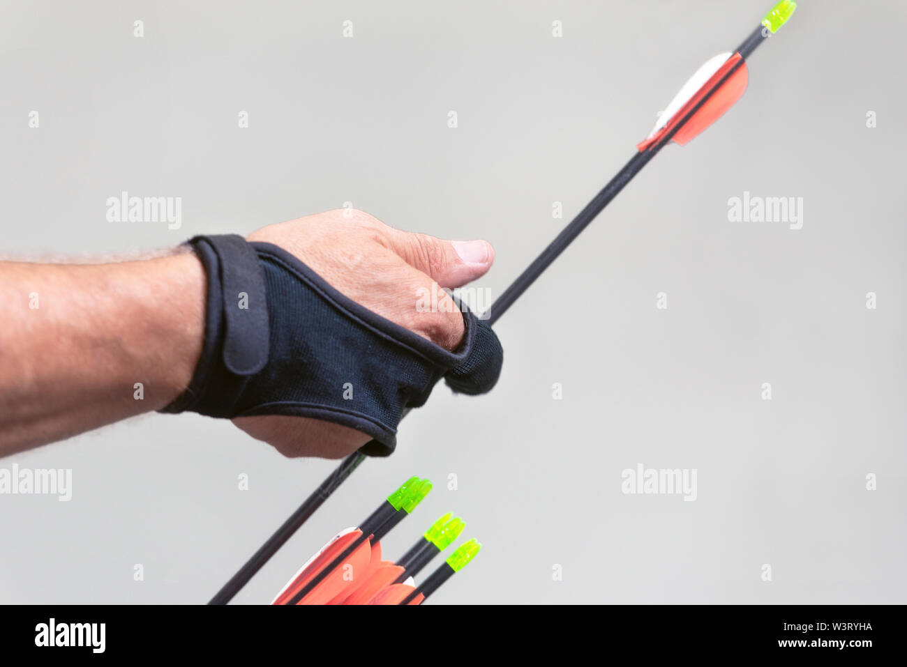 Archery. Archer exercise with the bow. Sport, recreation concept. Sportsman is preparing the arrow for the shot . - Stock Image