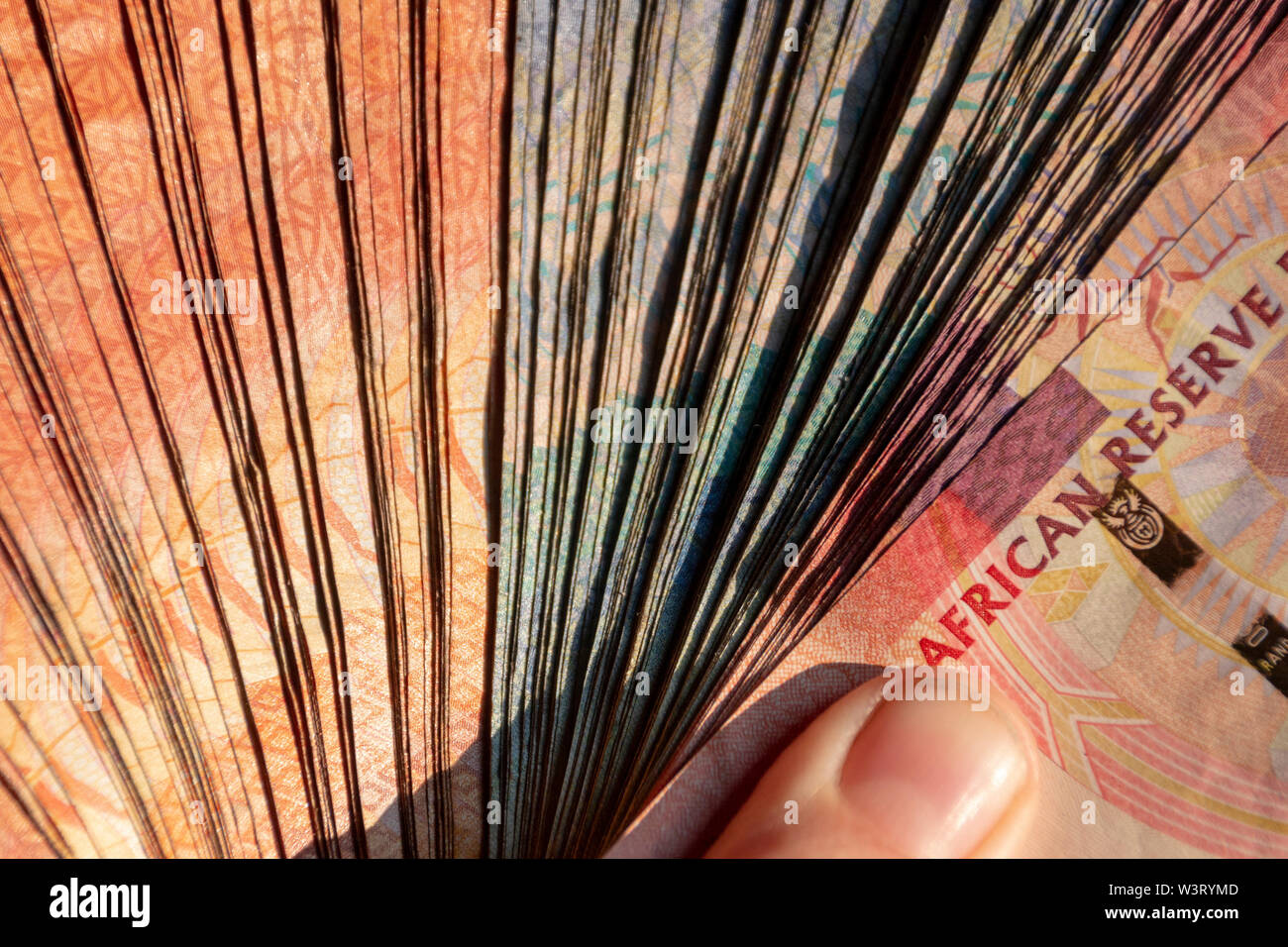 A close up of a pile of two hundred, one hundred and fifty rand sound african notes all spread out in a pile - Stock Image