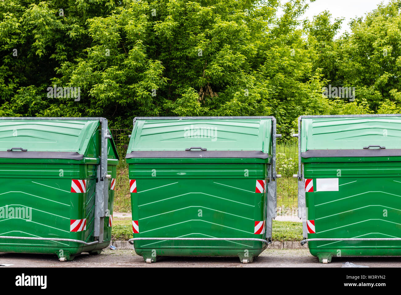 Three green recycle bins in row, outdoors. Environment and pollution concept. - Stock Image