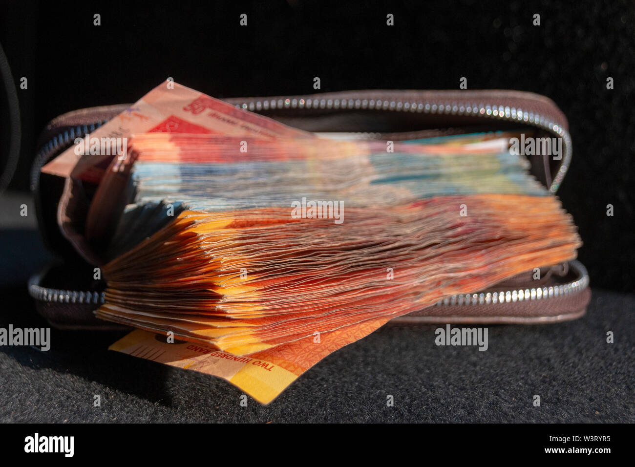 A close up view of pile of two hundred, one hundred and fifty rand sound african notes coming out the front of a brown leather wallet on a isolated ba - Stock Image