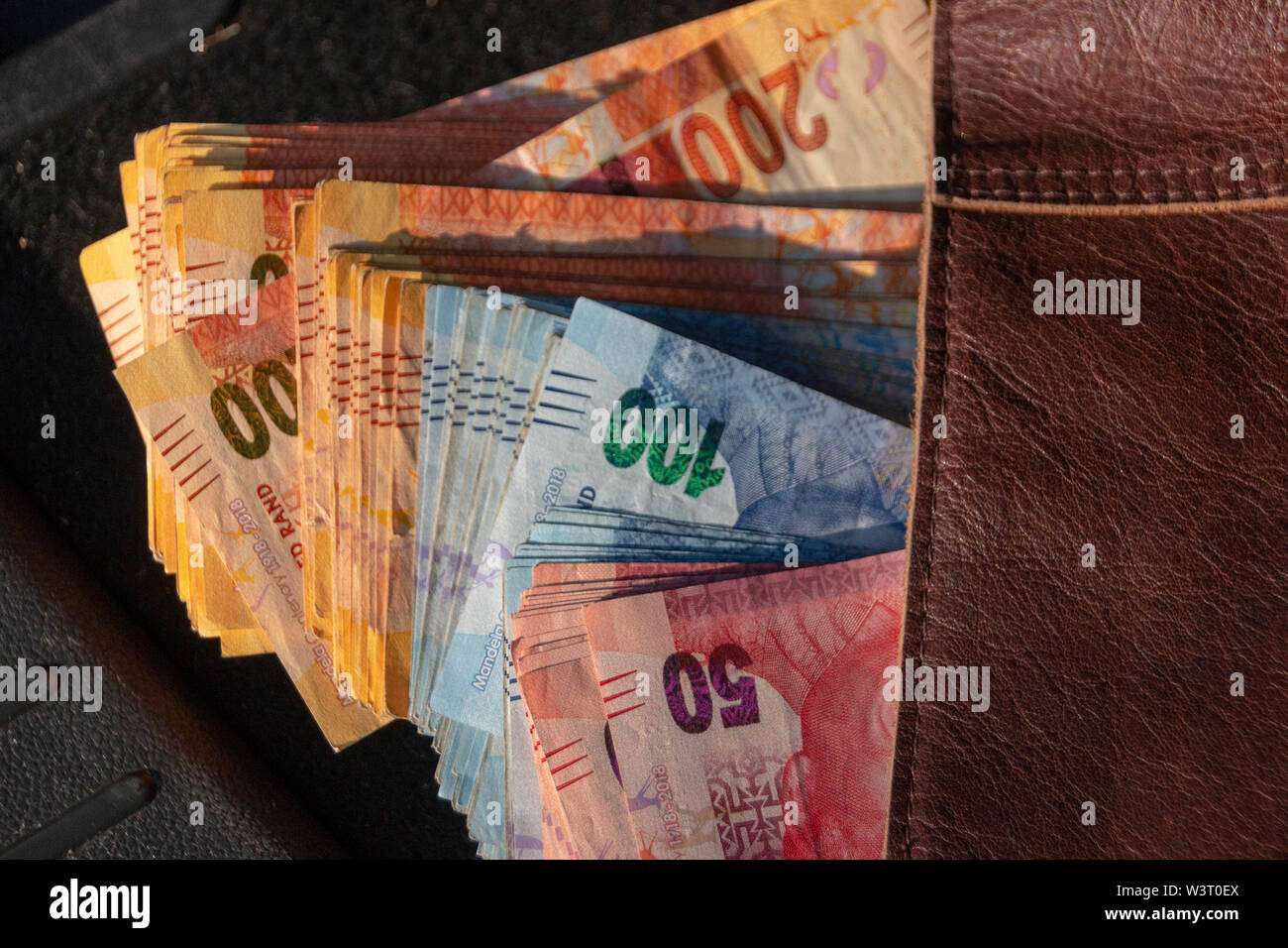 A close up view of pile of two hundred, one hundred and fifty rand sound african notes coming out the front of a brown leather handbag - Stock Image