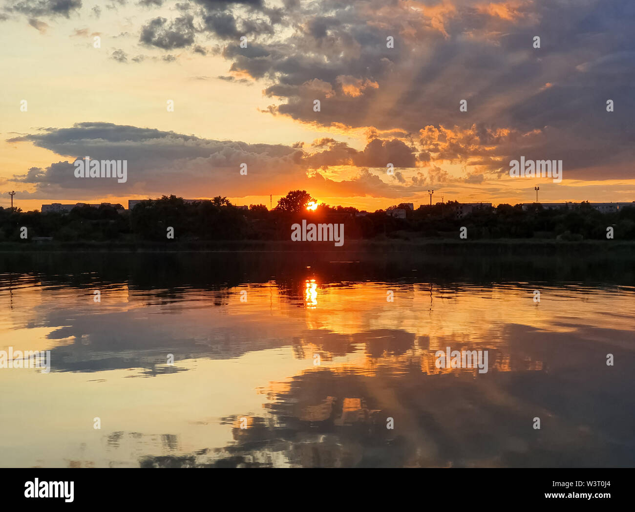 Wonderful sunset over the city horizon with reflection on the calm lake water in a silent summer evening. - Stock Image