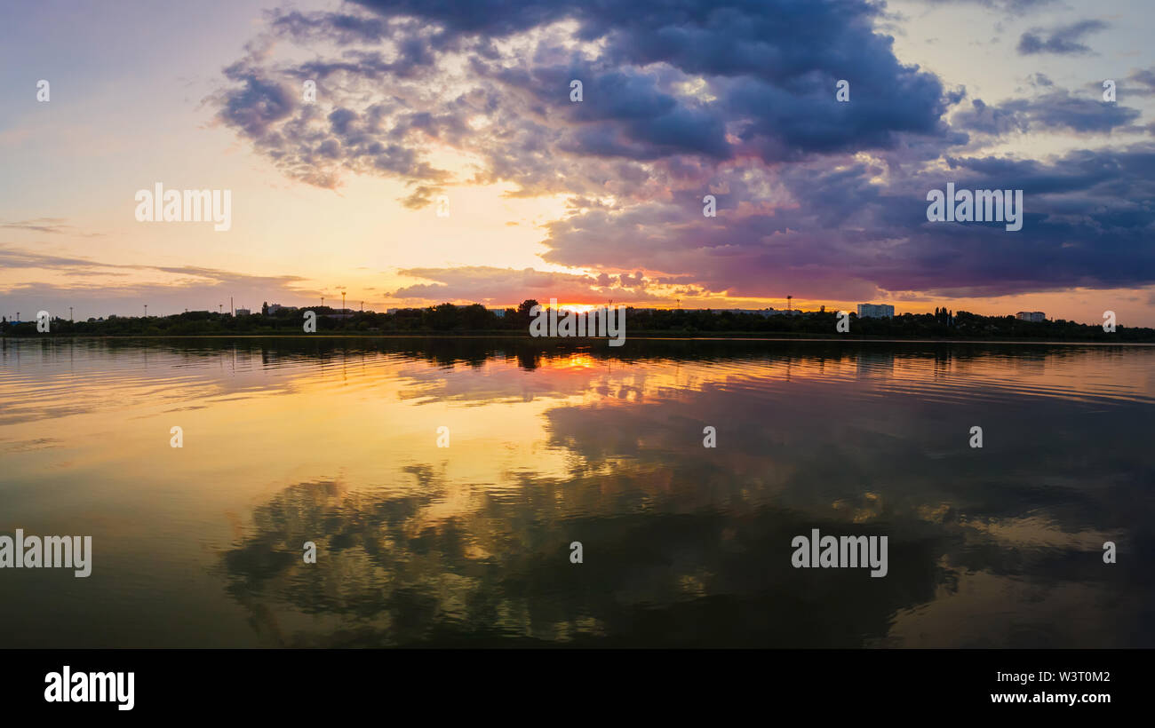 Wonderful sunset panorama over the city horizon with reflection on the calm lake water in a silent summer evening. - Stock Image