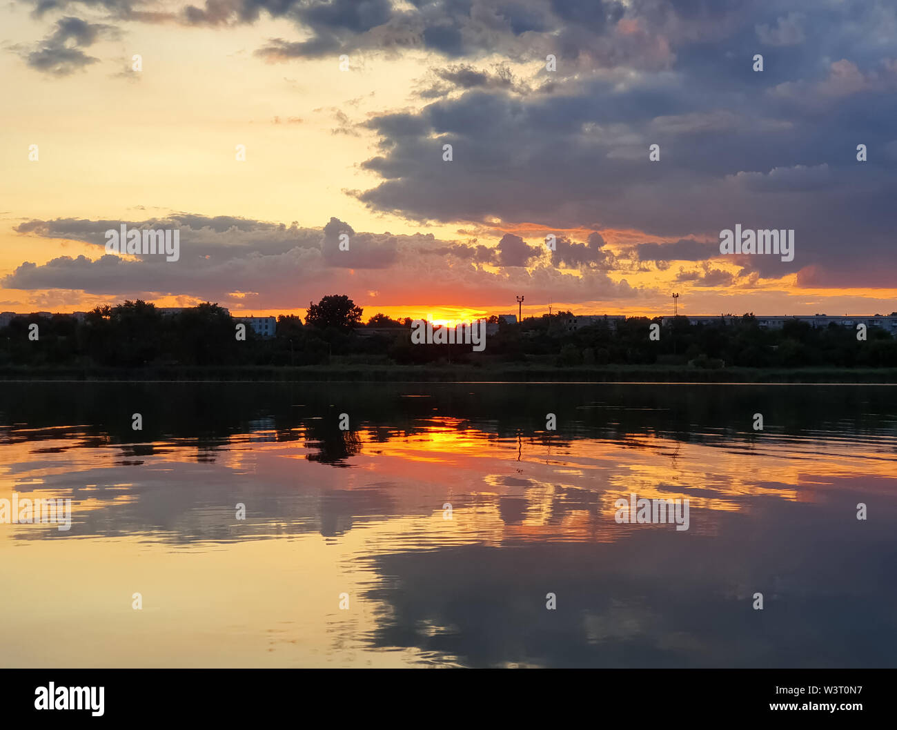 Beautiful sunset over the city horizon with reflection on the calm lake water in a silent summer evening. - Stock Image