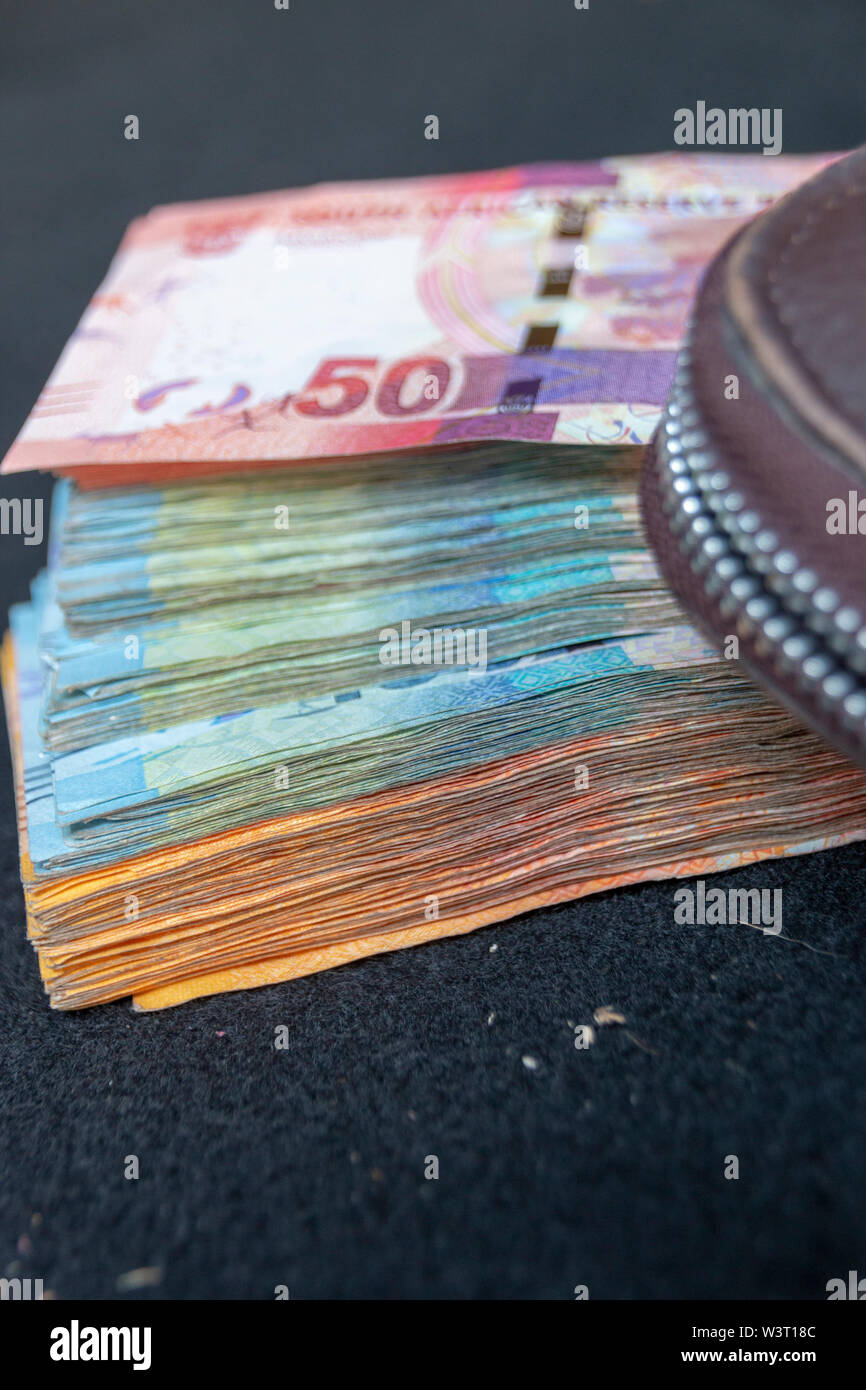 A close up view of pile of two hundred, one hundred and fifty rand sound african notes spread out next to a brown leathe wallet - Stock Image