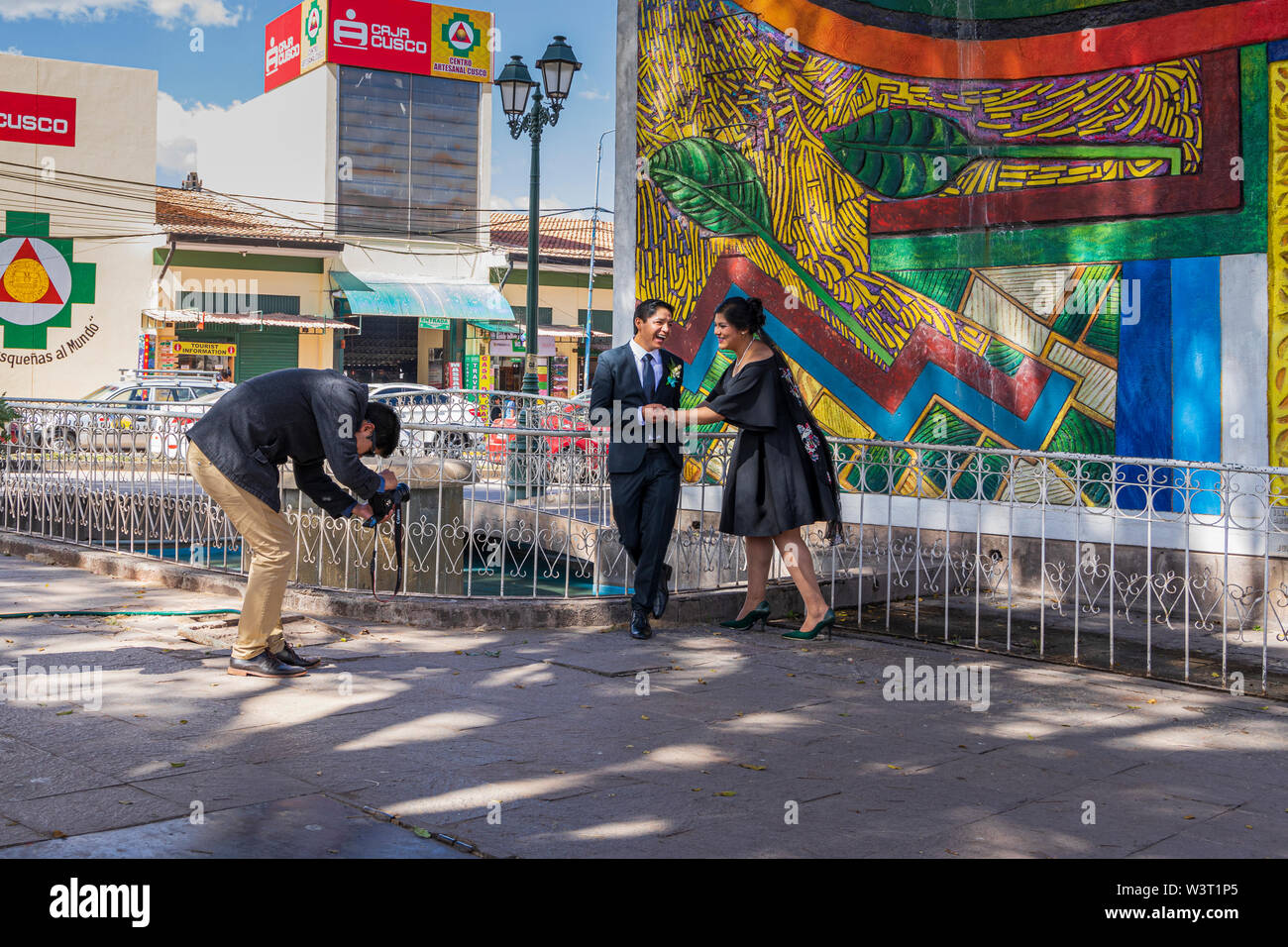 Wedding couple dressed in black being photographed in front of a colourful mural in Cusco, Peru, South America - Stock Image