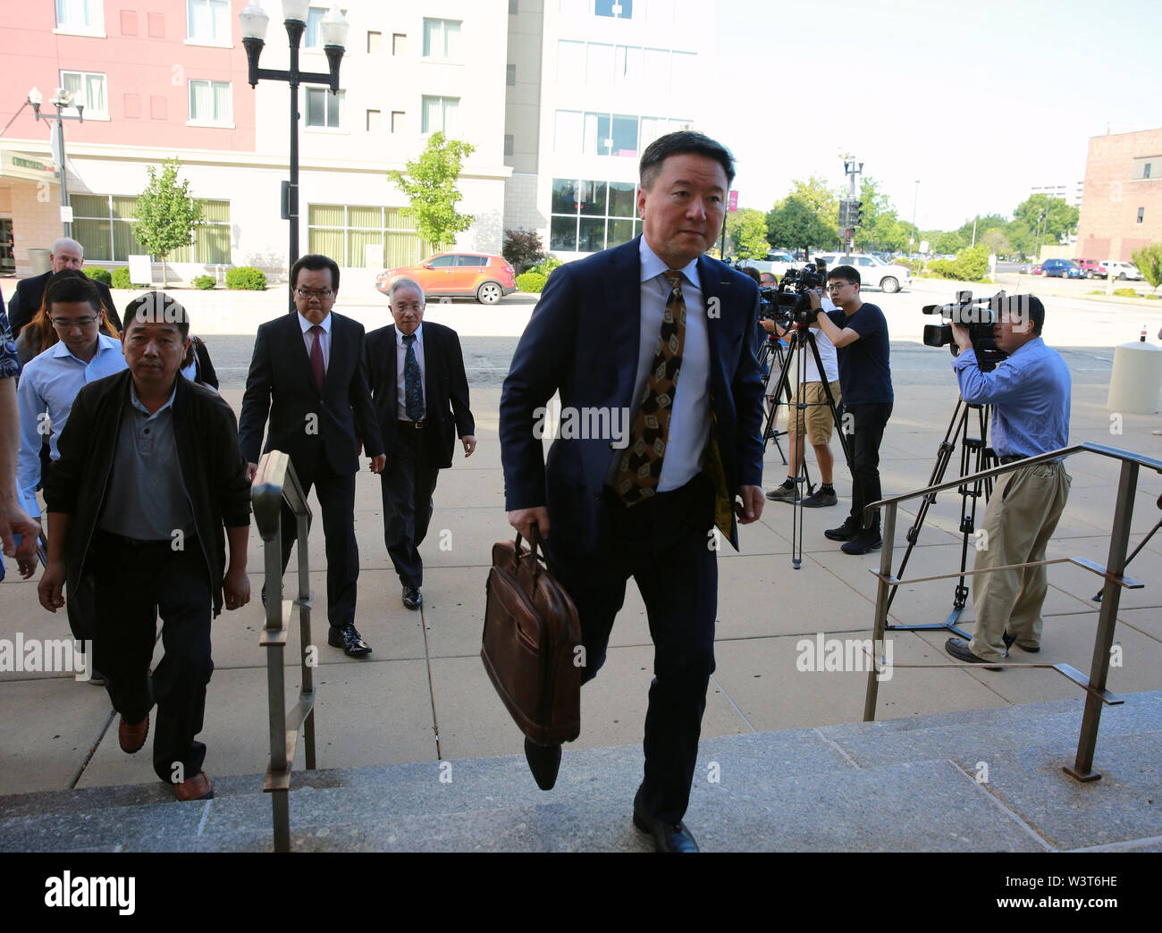 (190717) -- PEORIA (U.S.), July 17, 2019 (Xinhua) -- Wang Zhidong (Front), legal adviser to the family of visiting Chinese scholar Zhang Yingying, heads to the federal courthouse building in Peoria, Illinois, the United States, on July 17, 2019. After a U.S. judge concludes all the evidence from the sentencing phase in the Chinese scholar slaying trial Tuesday, closing arguments from both prosecutors and the defense started here Wednesday morning. The closing arguments of the sentencing phase for Brendt Christensen who was found guilty of killing Zhang Yingying in 2017 took place around 9 a.m. - Stock Image