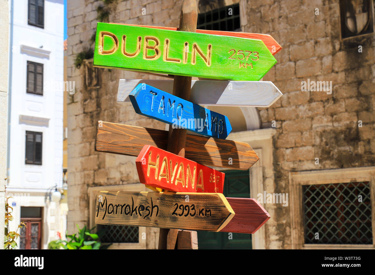 Tourism and travel concept. Colorful wooden road sign pointing directions and distances to different cities and countries - Havana, Dublin, Costa Rica - Stock Image
