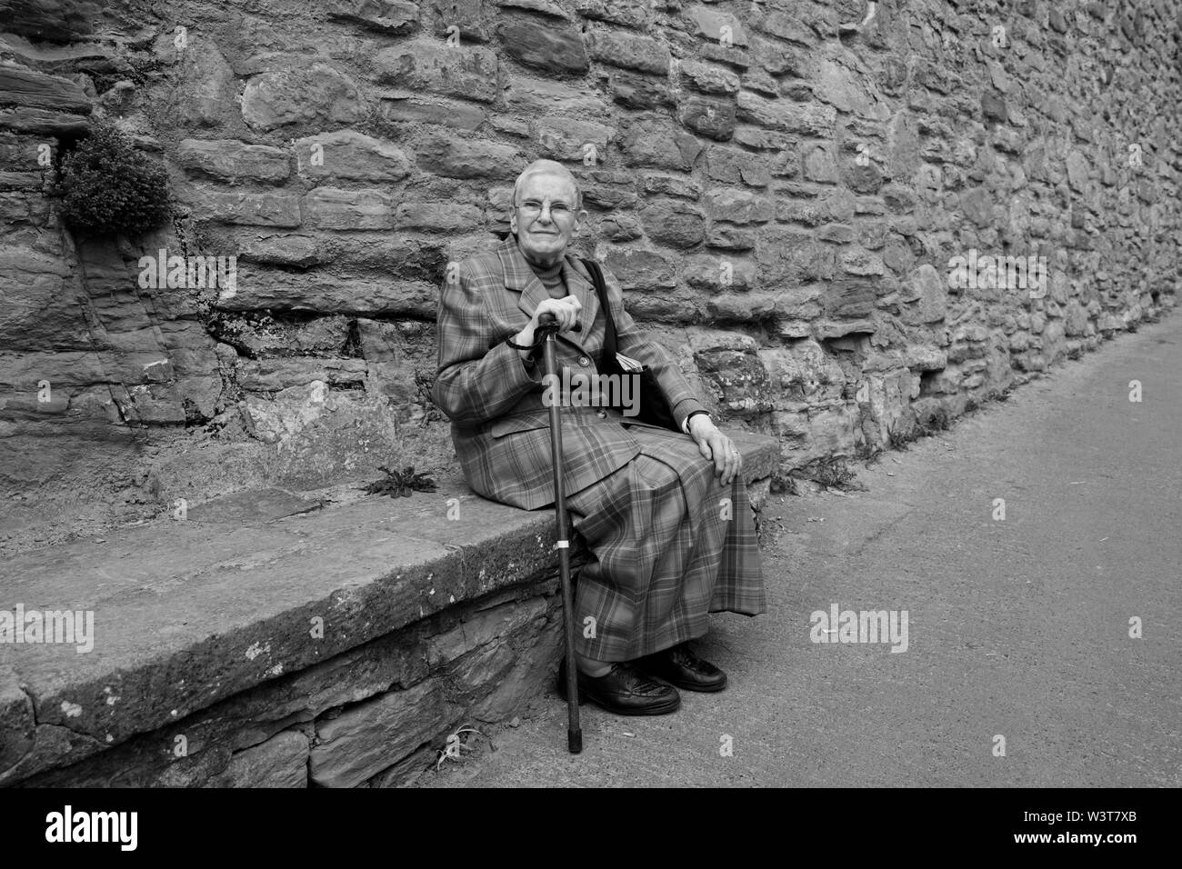 Elderly lady sitting on stone seat taking a well earned rest on the steep climb into Ludlow - Stock Image