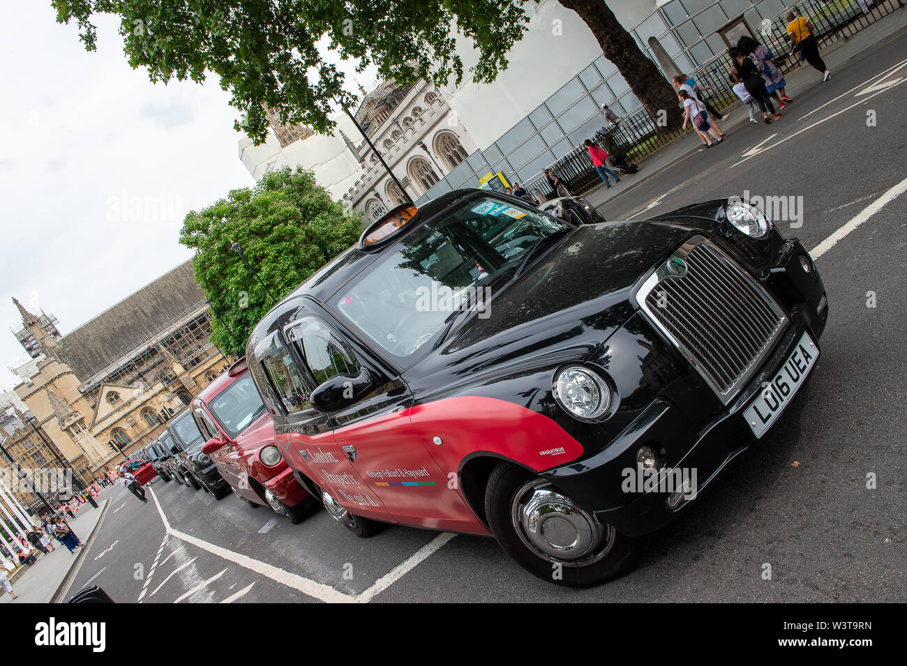 "Taxi Driver Protest, Westminster Square, London, UK. 17th July, 2019. Taxi drivers brought Westminster and the the surrounding area to a halt this afternoon as part of their weekly protest by blocking the roads  around Parliament Square with their black cabs. TFL plan to stop taxi drivers from using some roads around London and London cabbies are not happy about it. Their message is ""Where buses go, taxis go"".  Credit: Maureen McLean/Alamy Live News Stock Photo"