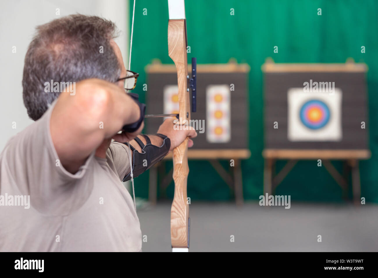 Senior Archer Training With The Bow. Shooting the target in the background . - Stock Image