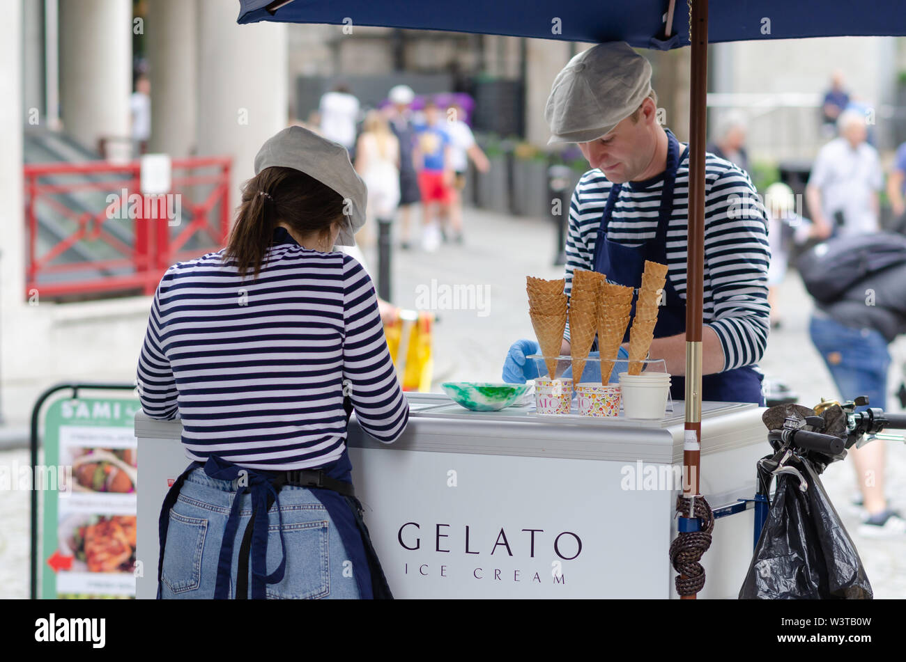 Young girl and a man are selling Gelato ice cream in the London street, near to the Tower Bridge. Stock Photo