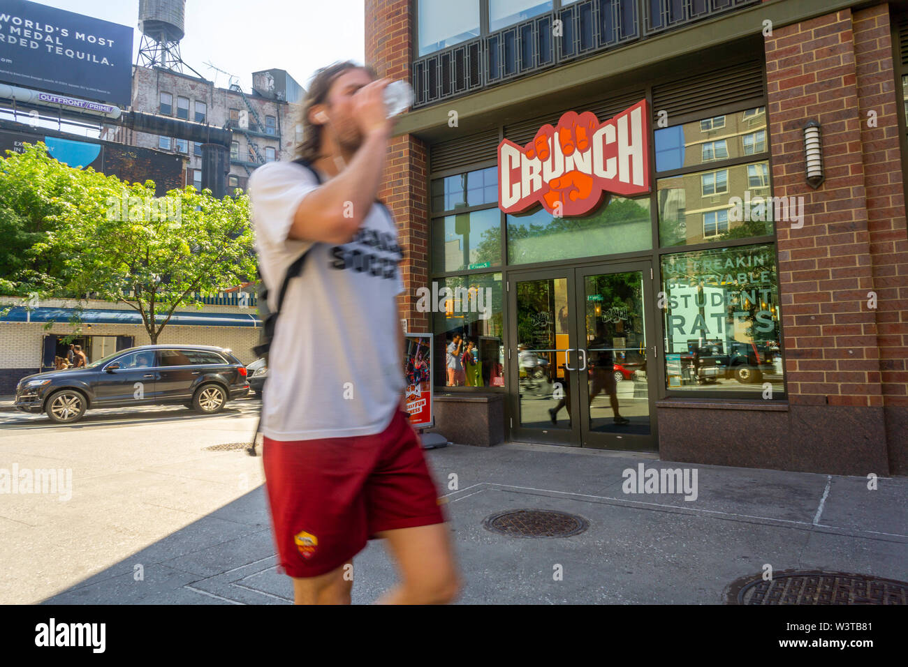 People pass a branch of Crunch Fitness in the East Village neighborhood of New York on Saturday, July 13, 2019. Crunch Fitness has been recently sold to the private equity firm TPG for an undisclosed amount. (© Richard B. Levine) - Stock Image