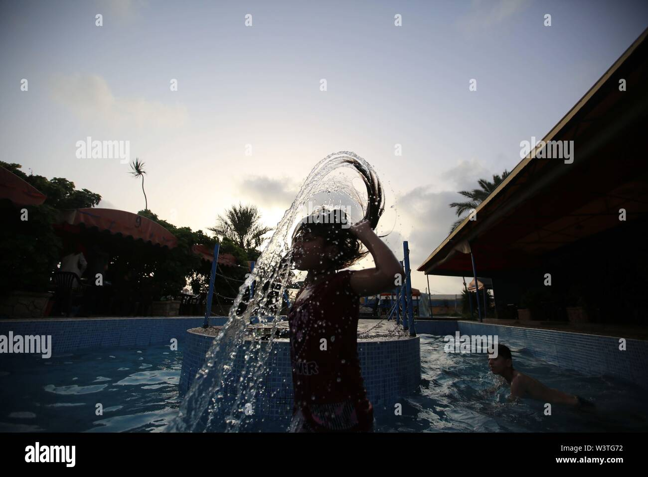 July 17, 2019 - Gaza City, The Gaza Strip, Palestine - A Palestinian girl wave her wet hair at a swimming pool on a hot day in the Gaza Strip. (Credit Image: © Hassan Jedi/Quds Net News via ZUMA Wire) - Stock Image