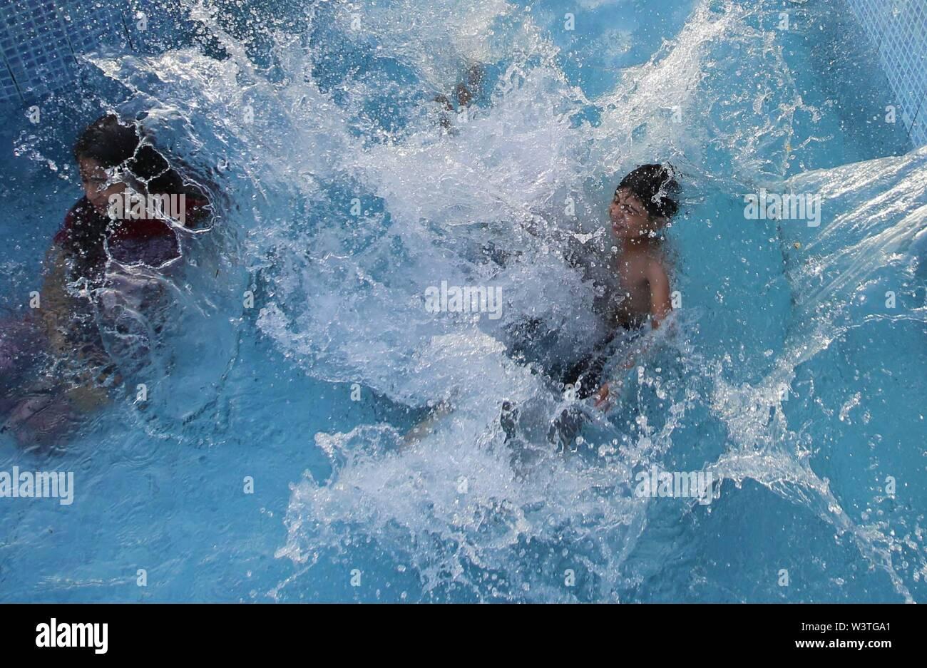 Gaza City, The Gaza Strip, Palestine. 17th July, 2019. Palestinian children play at a swimming pool on a hot day in the Gaza Strip. Credit: Hassan Jedi/Quds Net News/ZUMA Wire/Alamy Live News - Stock Image