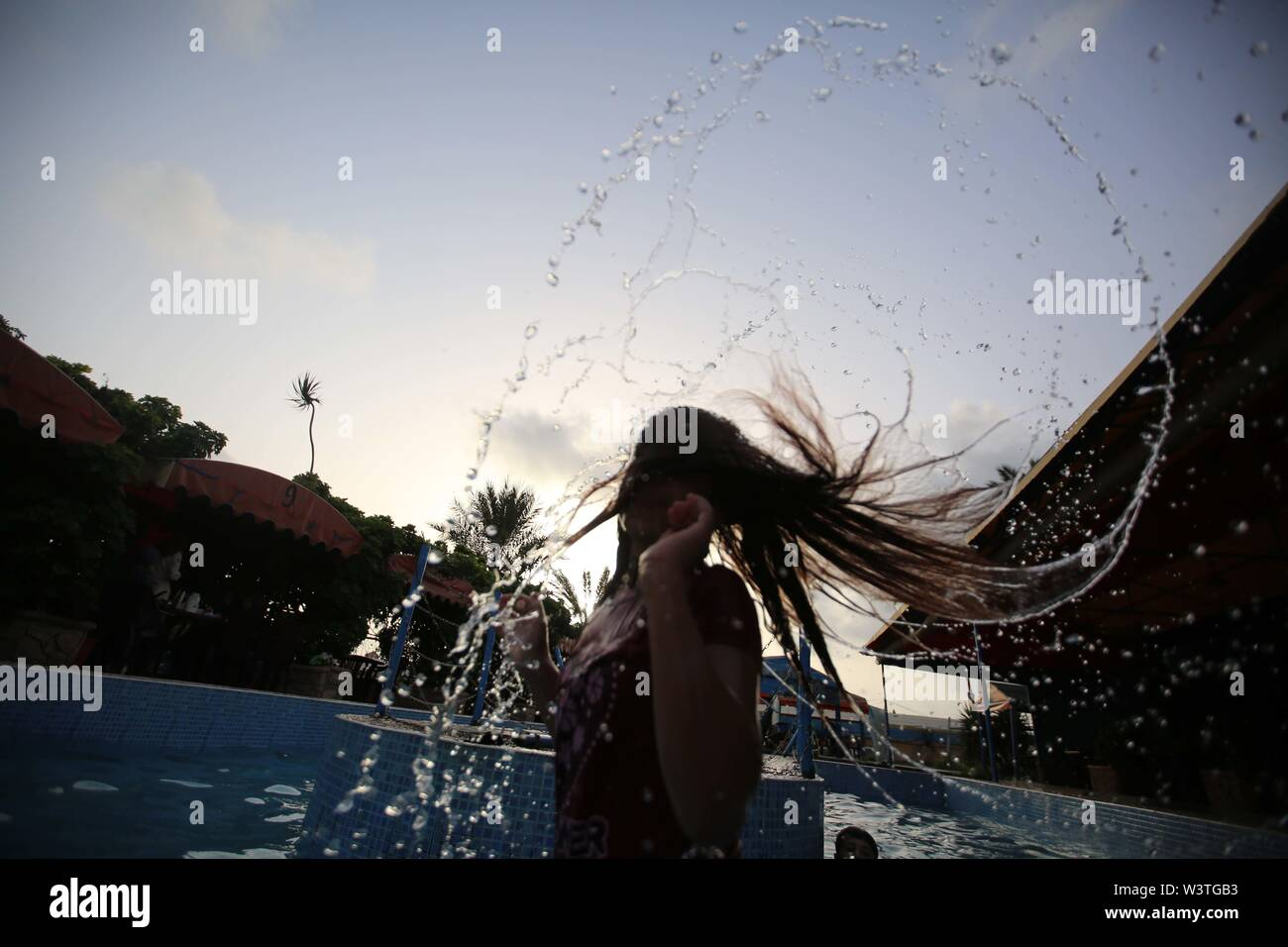 Gaza City, The Gaza Strip, Palestine. 17th July, 2019. A Palestinian girl wave her wet hair at a swimming pool on a hot day in the Gaza Strip. Credit: Hassan Jedi/Quds Net News/ZUMA Wire/Alamy Live News - Stock Image