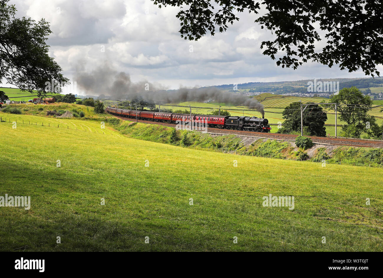 45690 Leander heads past Benson Hall near Oxenholme with a Cumbrian Mountain express. - Stock Image