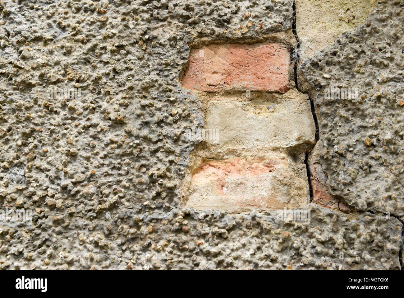 Bricks showing where weather has eroded away at the rendering causing it to come away from the wall - Stock Image
