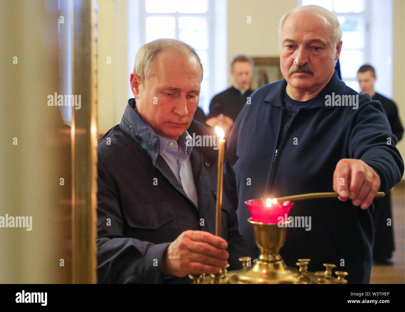Russia. 17th July, 2019. LENINGRAD REGION, RUSSIA - JULY 17, 2019: Russia's President Vladimir Putin (L) and Belarus' President Alexander Lukashenko light candles on their visit to the Konevsky Monastery on Lake Ladoga. Mikhail Klimentyev/Russian Presidential Press and Information Office/TASS Credit: ITAR-TASS News Agency/Alamy Live News - Stock Image