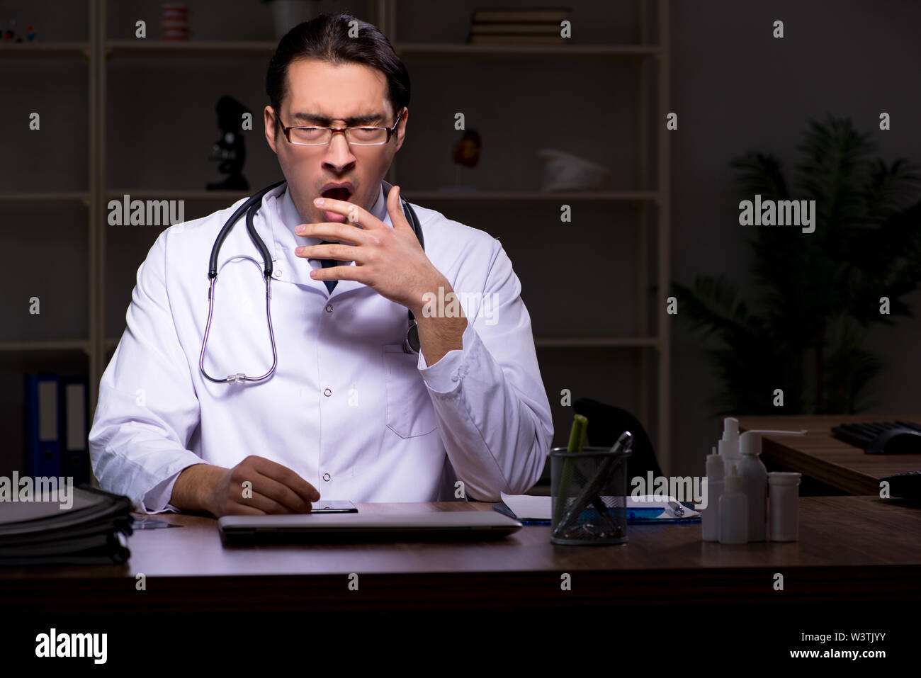 The young male doctor in the hospital at night - Stock Image