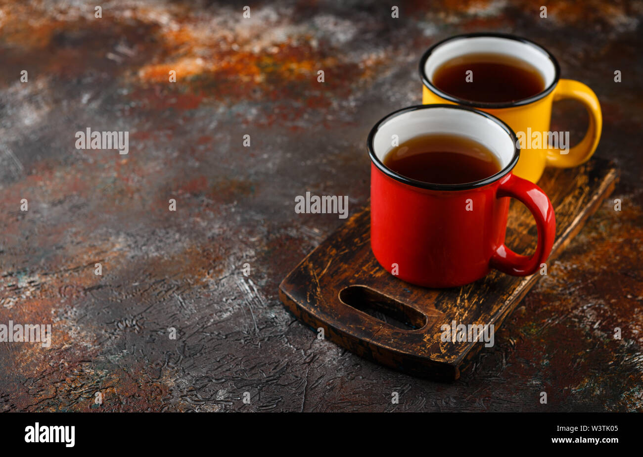 Two colored enamel tea cups on rusty brown background - Stock Image