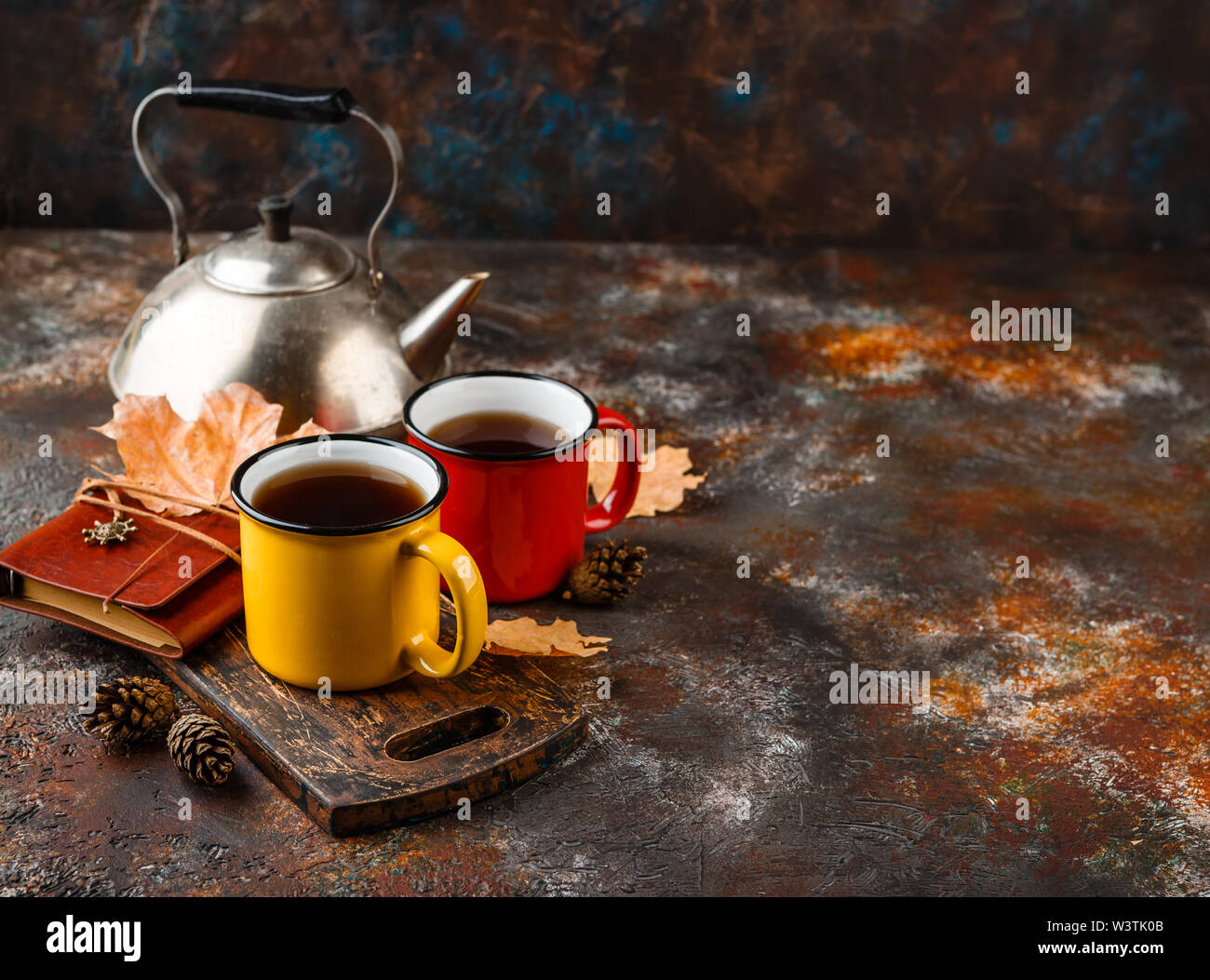 Two colored enamel tea cups, autumn maple leaves and pine cones on a rusty brown background - Stock Image