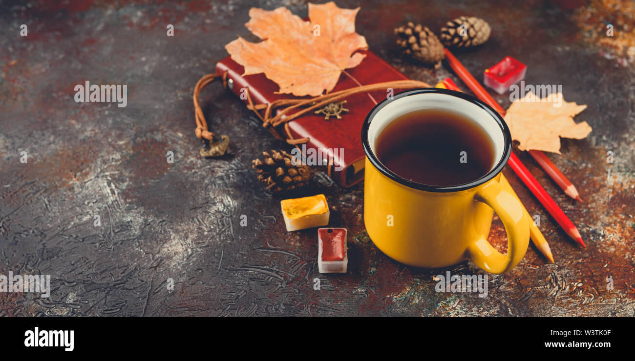 Yellow enamel cups of tea, watercolors in cuvettes, colored pencils, autumn maple leaves and bumps on a brown background - Stock Image