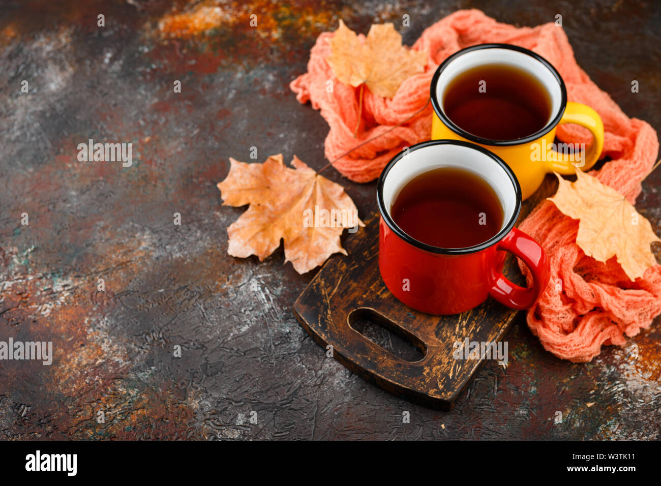 Two colored enamel tea cups, autumn maple leaves on rusty brown background - Stock Image