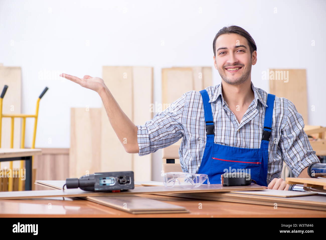 The young male carpenter working indoors - Stock Image