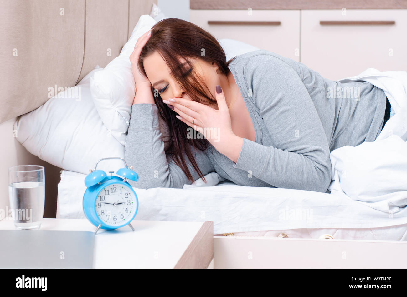 The young woman lying on the bed in time management concept - Stock Image
