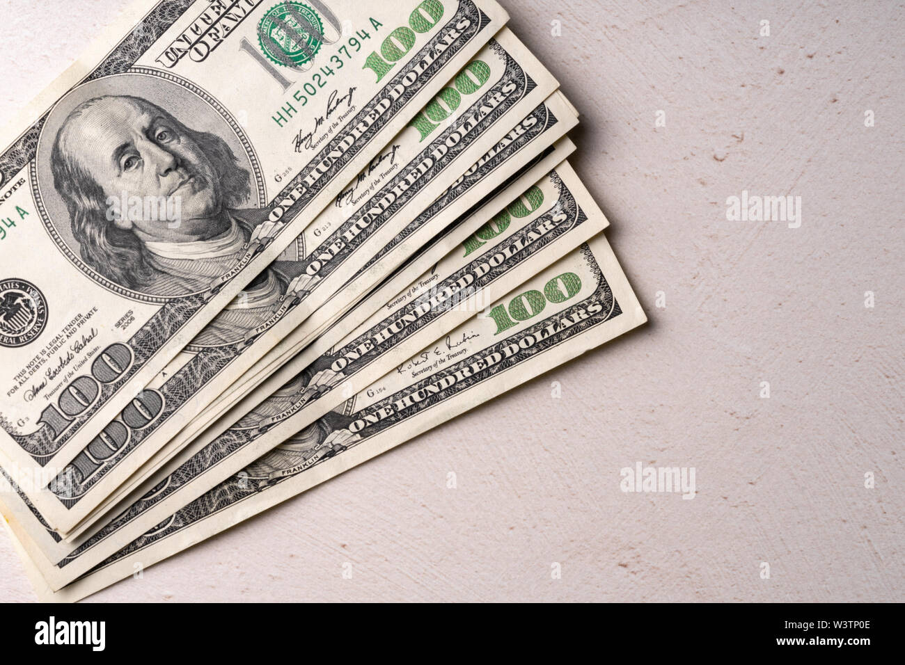 A fragment of a bill of 100 US dollars.Several bills on a white background - Stock Image