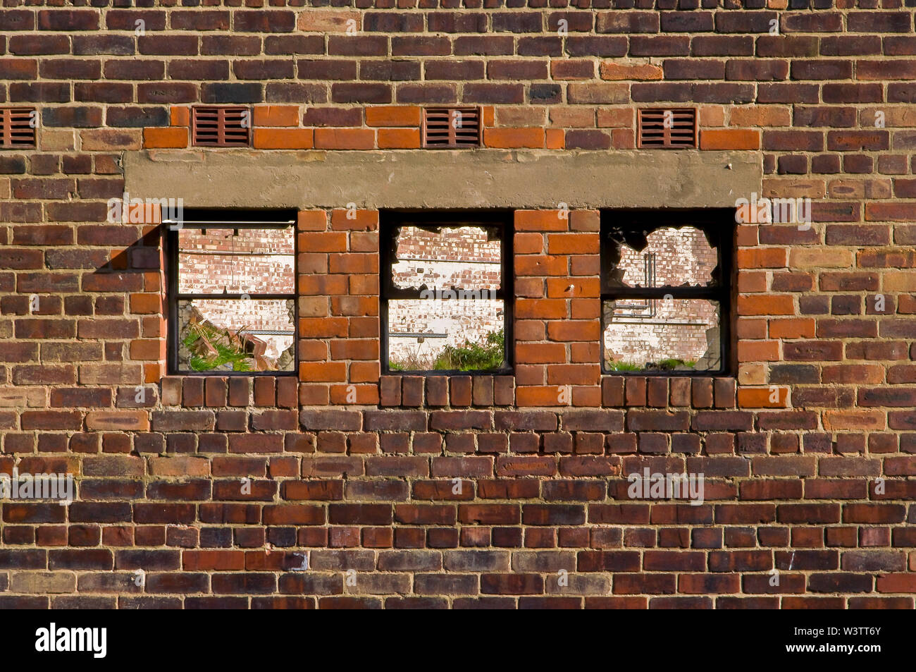 Three empty windows in the brick wall of a disused factory building Stock Photo