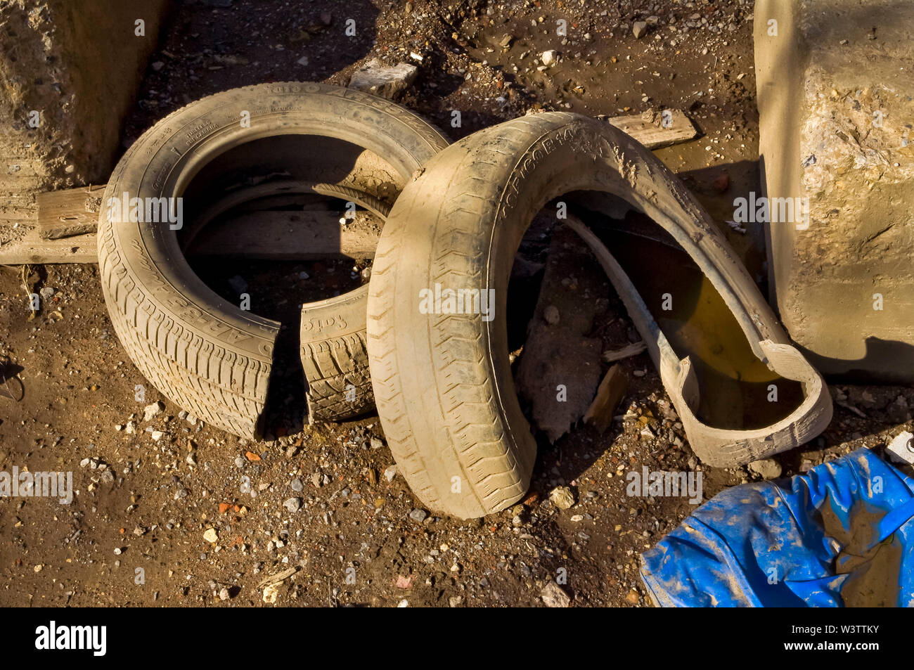 Two Car tyres dumped on waste ground in bright sunshine Stock Photo