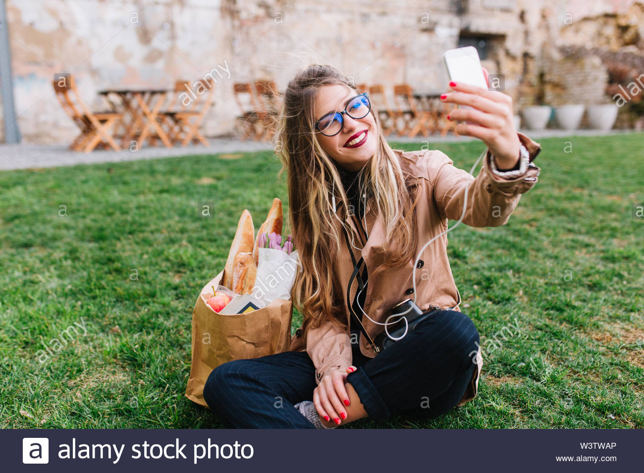Cute blonde girl in glasses making selfie with hand up sitting on the green grass in park. Charming young woman taking rest after shopping and making photo for instagram profile with legs crossed - Stock Image