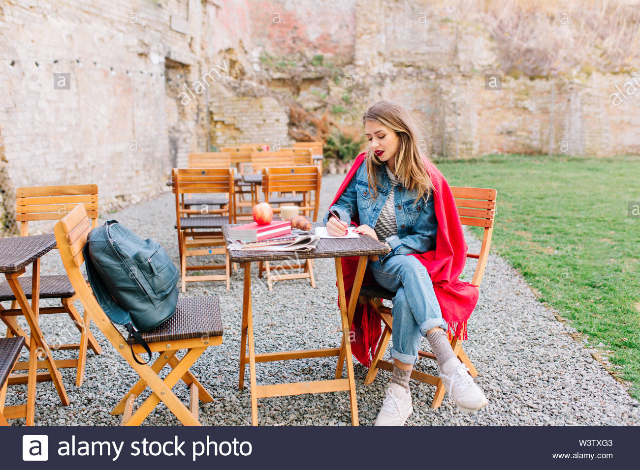 A beautiful girl with blonde hair, in denim suit sitting in the cozy cortyard writes personal notes...Young woman, thoughtfully, stylish outfit - Stock Image