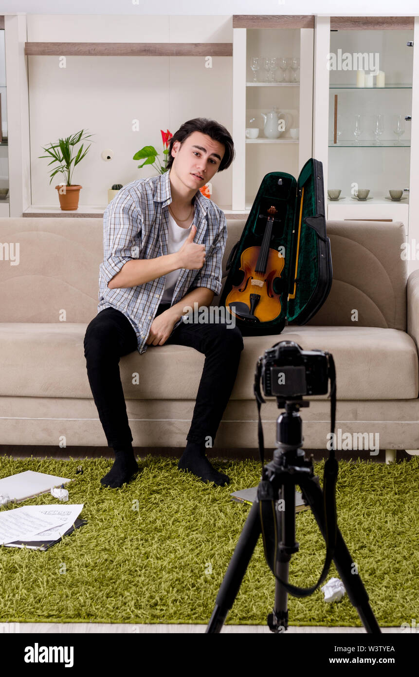 The young male blogger playing violin at home - Stock Image