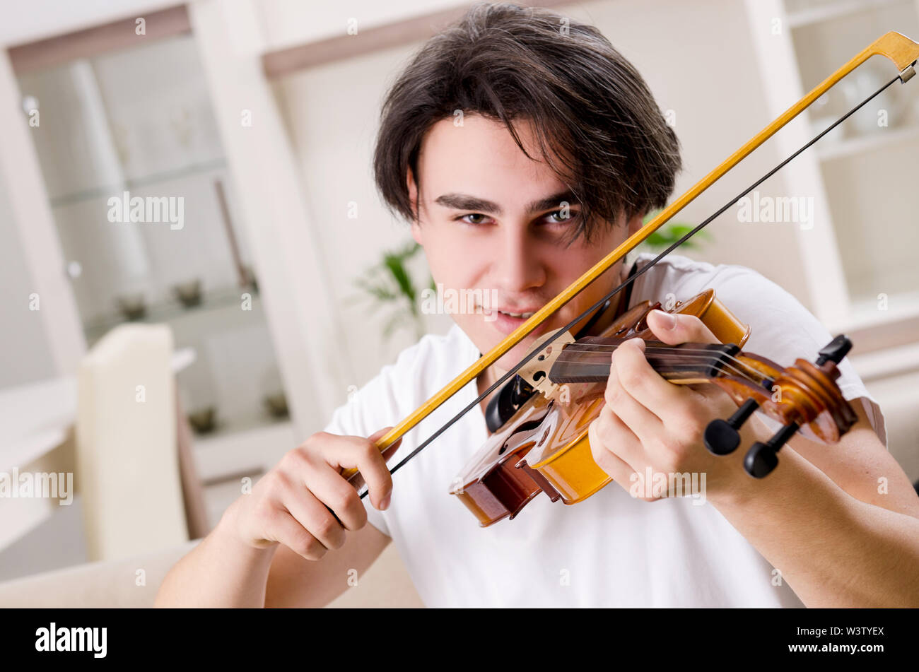 The young musician man practicing playing violin at home - Stock Image