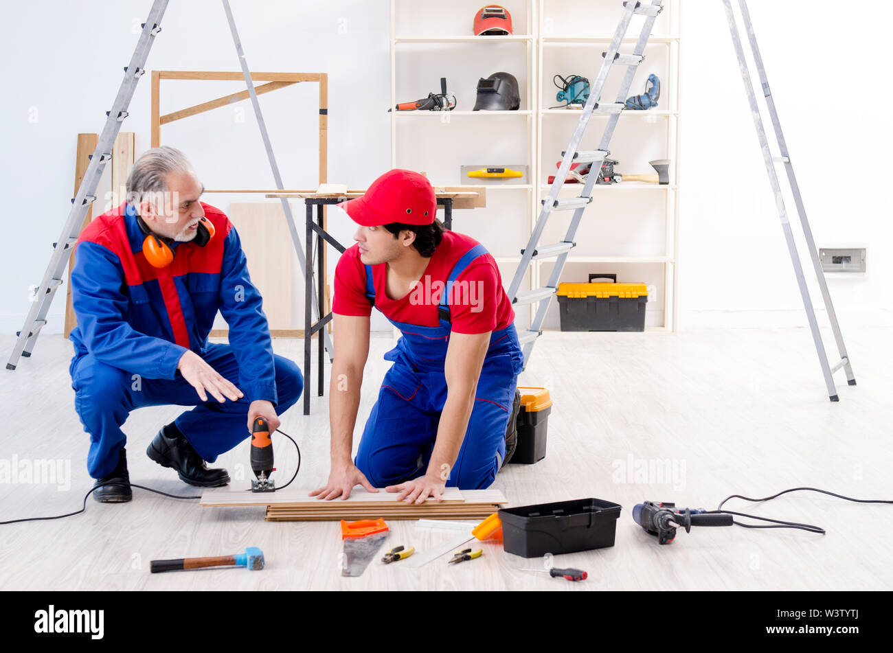 The two professional contractors laying flooring at home - Stock Image