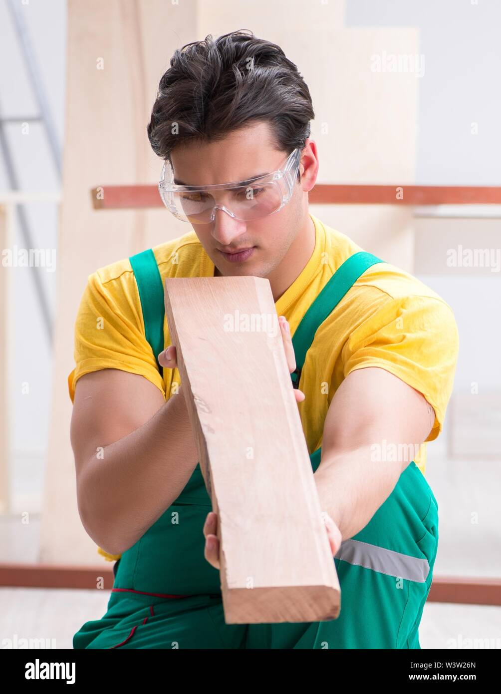 The contractor working on laminate wooden floor - Stock Image