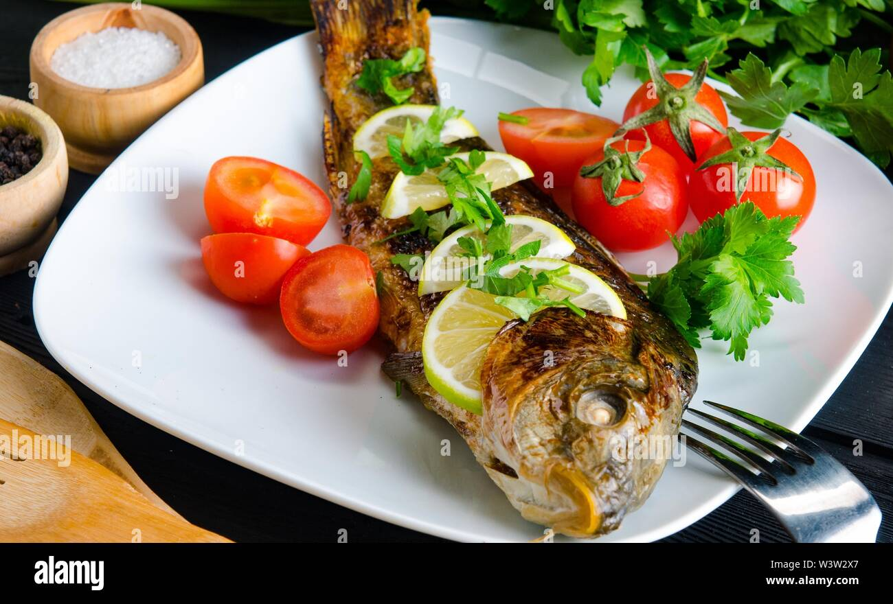 The fried fish served on the plate - Stock Image