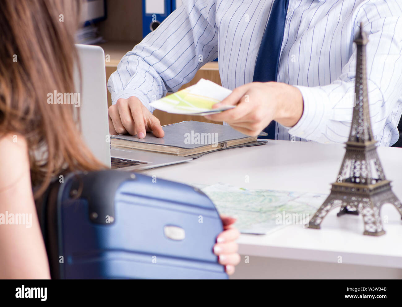 The male travel agent with customer in agency - Stock Image