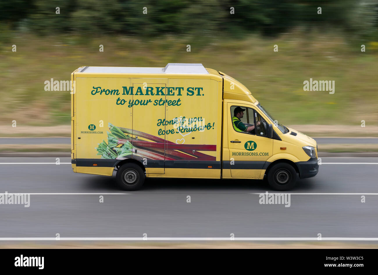 A Morrison's delivery van travels along an A road in Alderley Edge, Cheshire, UK. - Stock Image