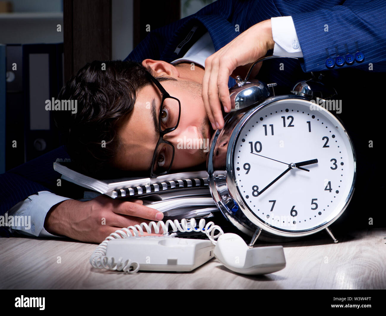 The businessman working overtime long hours late in office - Stock Image