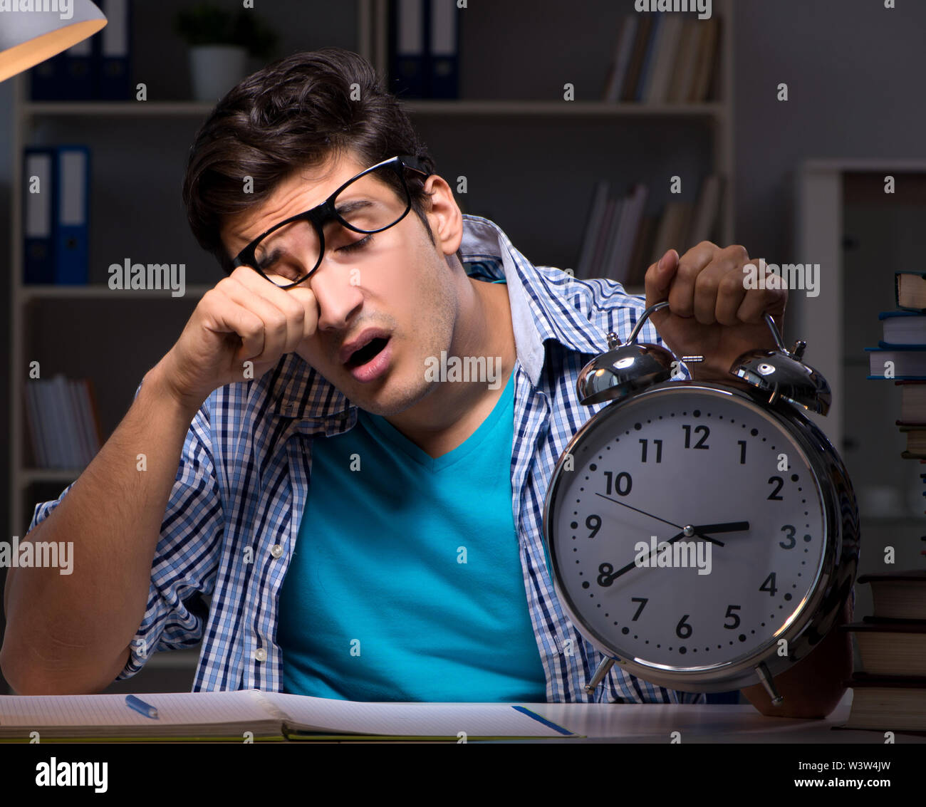 The student preparing for exams late night at home - Stock Image
