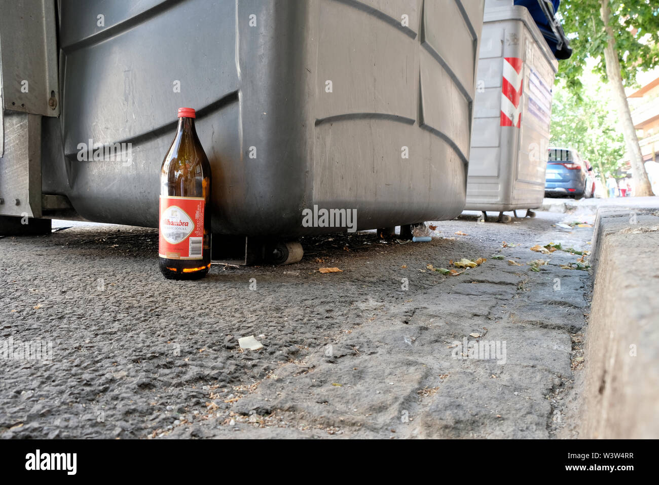 A one litre bottle of Alhmabra tradicional beer abandoned by the side of the street near a trash bin and sidewalk in Granada, Spain. - Stock Image
