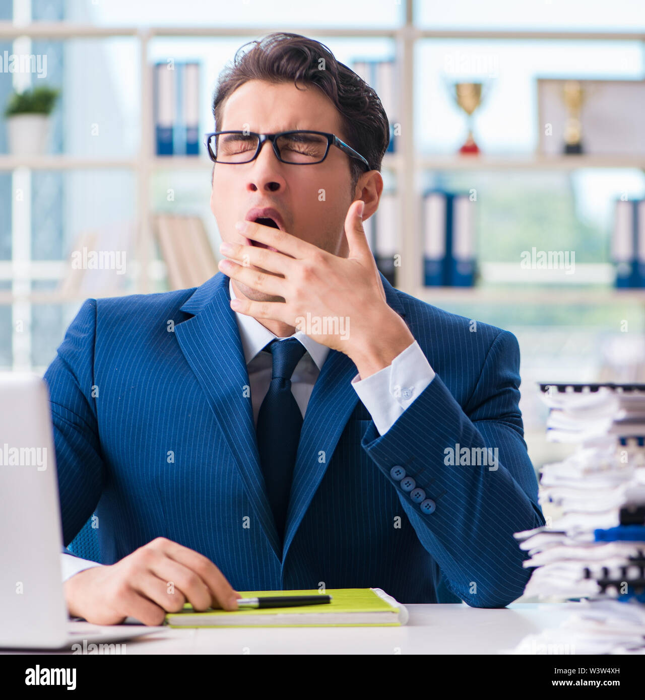 Tired businessman exhausted after hard work and excessive workload - Stock Image
