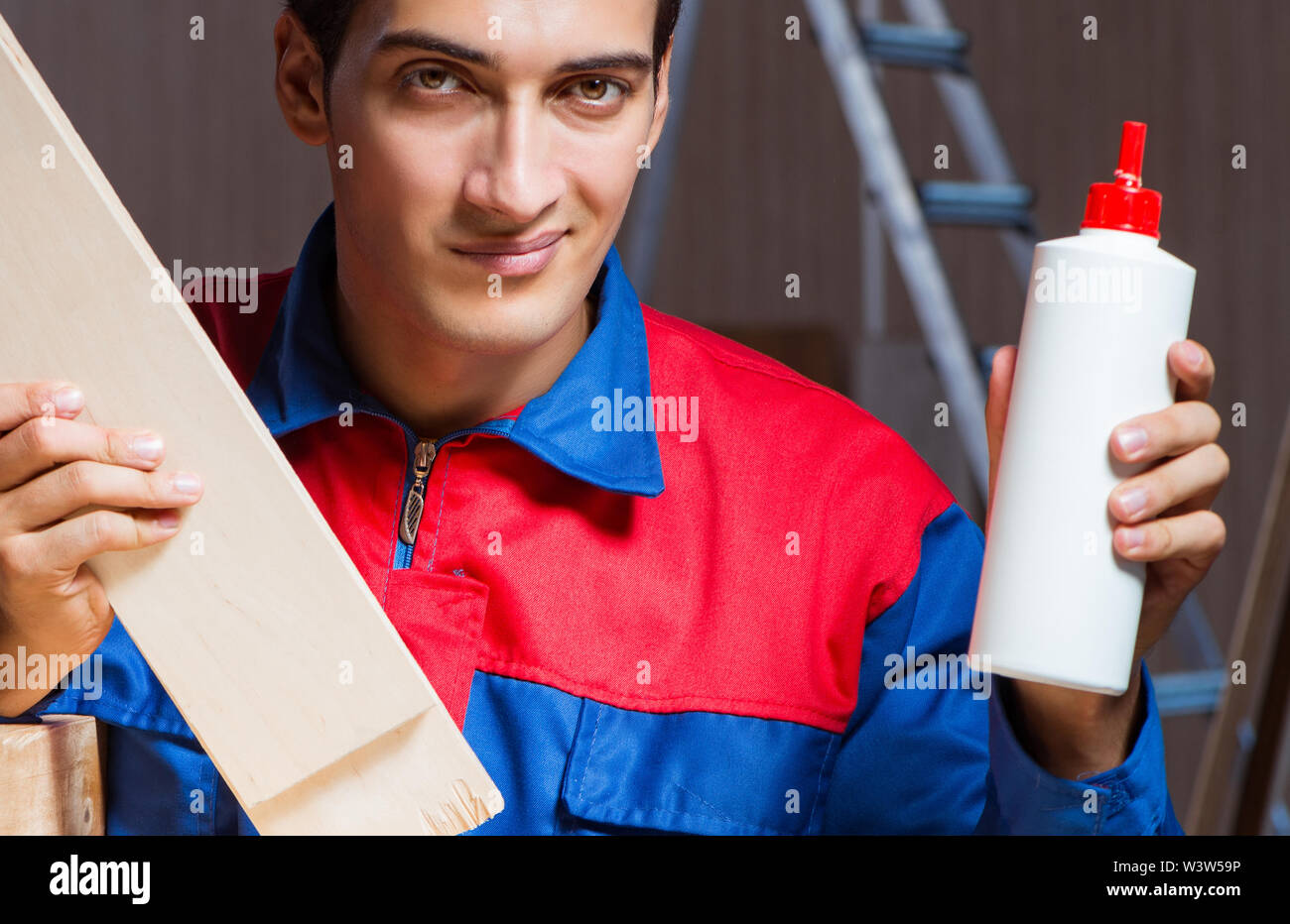 The young man gluing wood pieces together in diy concept - Stock Image
