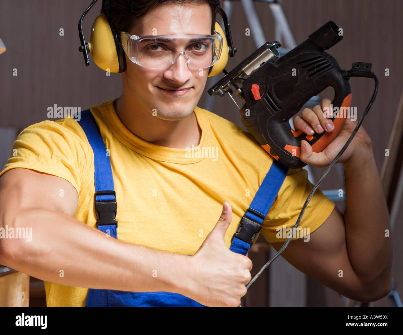 The worker working in repair workshop in woodworking concept - Stock Image