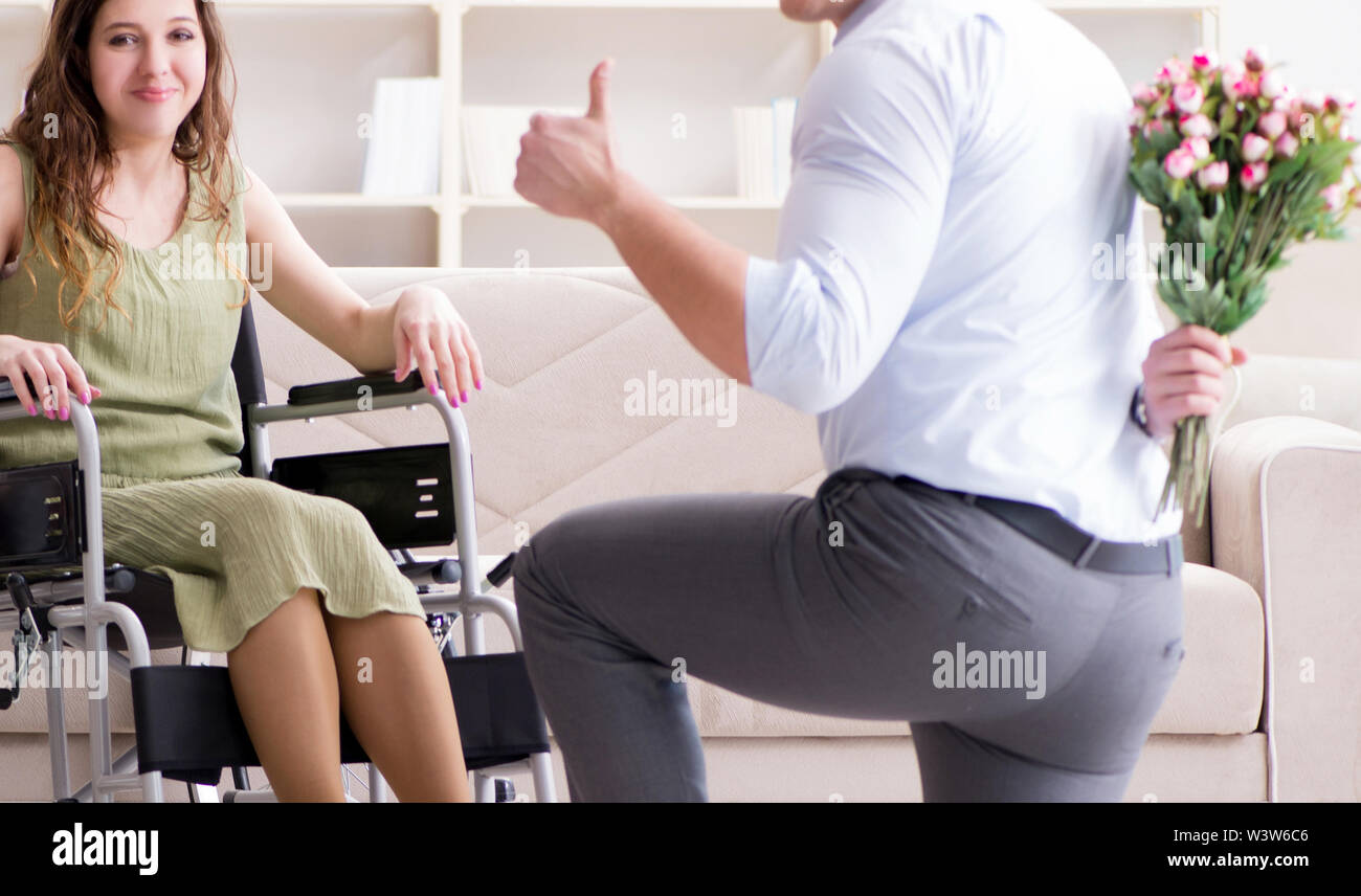 The man making marriage proposal to disabled woman on wheelchair - Stock Image
