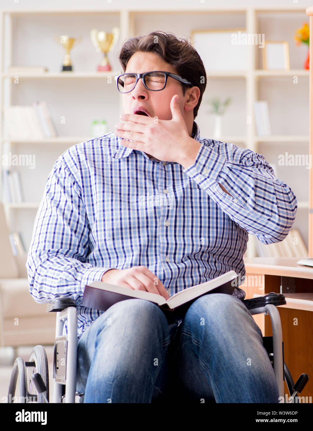 The disabled student studying at home on wheelchair - Stock Image